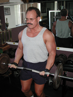 Persnal trainer Tim Dugas curls a barbell.